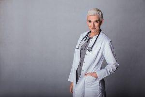 Lekarz medycyny estetycznej Beata Hill Wadas - zdjęcie wfartuchu izestetoskopem naszarym tle