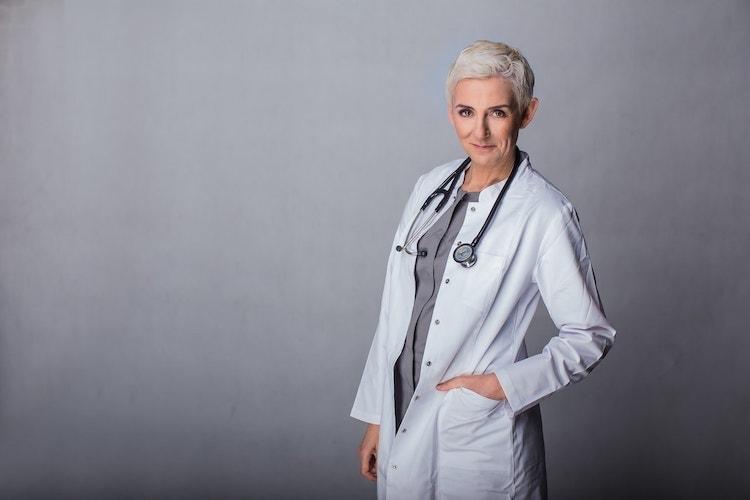 Lekarz medycyny estetycznej Beata Hill Wadas - zdjęcie w fartuchu i ze stetoskopem na szarym tle