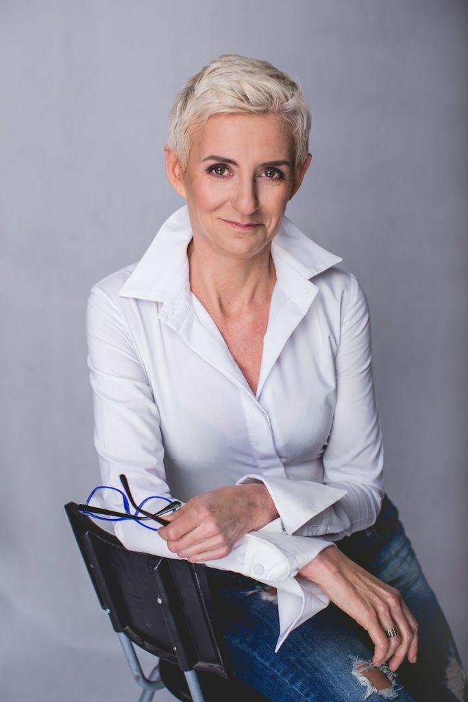Beata Hill Wadas - lekarz medycyny estetycznej weWrocławiu iautorka bloga, wbiałej koszuli, okulary wręce