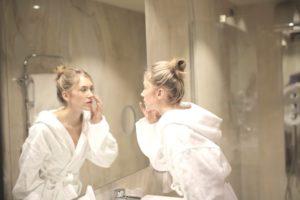 kobieta przedlustrem - zastanawia się nadzabiegiem medycyny estetycznej?